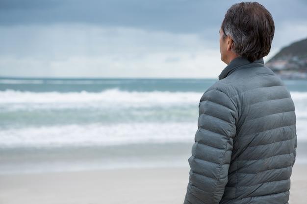 Uomo premuroso che sta sulla spiaggia