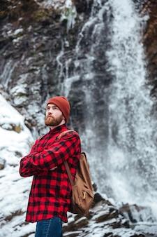 Uomo premuroso con zaino e braccia piegate in piedi vicino a una cascata all'aperto e guardando lontano