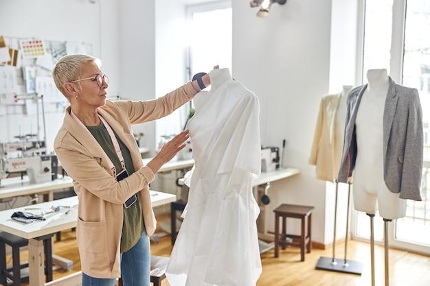 La sarta matura premurosa guarda il tessuto bianco con arricciature appuntate sul manichino in officina