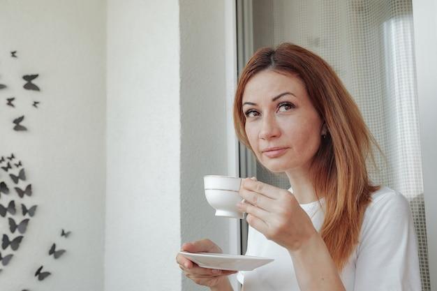 Premurosa donna matura sul balcone di casa sua con una tazza di caffè in mano e guardando lontano. la donna di mezza età beve il tè del mattino, pensando. concetto rilassati e pensa mentre bevi caffè