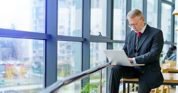Riflessivo uomo d'affari di mezza età in tuta. seduto vicino alla finestra in ufficio che lavora al computer portatile. sfondo di vista panoramica sulla città. foto di affari.