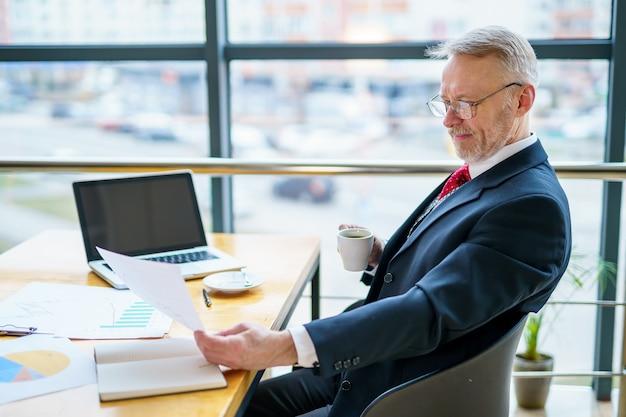 Riflessivo uomo d'affari di mezza età in tuta con un computer portatile sul tavolo mentre si lavora con i documenti.