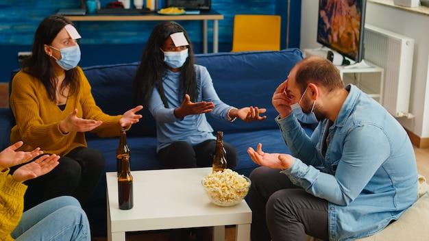 Amici multietnici premurosi con note adesive sulla fronte che giocano a giochi di nome mimando gesti indossando una maschera per il viso mantenendo le distanze sociali prevenendo la diffusione del covid19. persone che si godono le bottiglie di birra