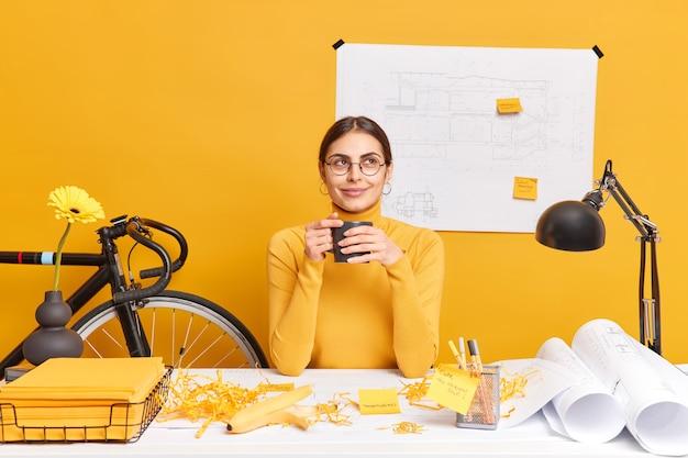 L'architetto femminile professionale premuroso beve il caffè pone al dekstop con lo schizzo della costruzione nel muro ha disordine sulla scrivania dell'ufficio pensa alla creazione di un nuovo progetto indossa occhiali e dolcevita