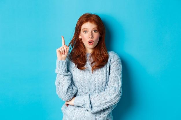 Premurosa ragazza rossa che ha un'idea, alzando il dito e dicendo suggerimento, in piedi su sfondo blu.