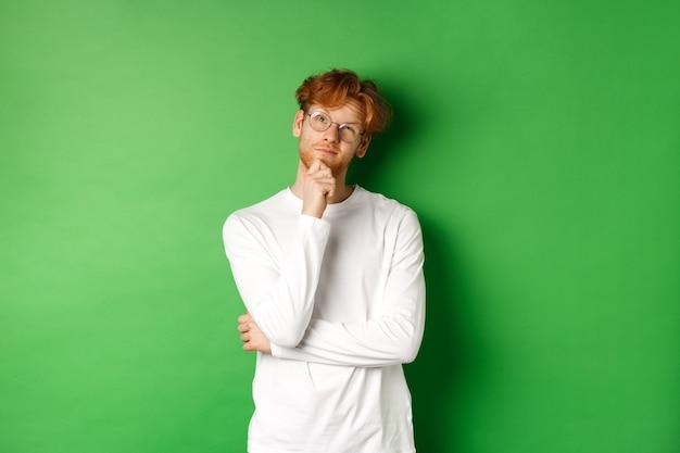 Uomo premuroso di redhead in vetri che fanno la scelta, guardando in alto e pensando, in piedi su sfondo verde.
