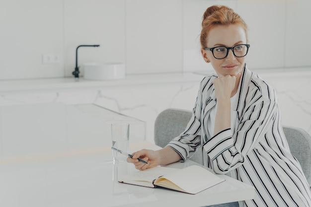 La donna rossa premurosa distratta dal lavoro prende appunti nel blocco note tiene la penna
