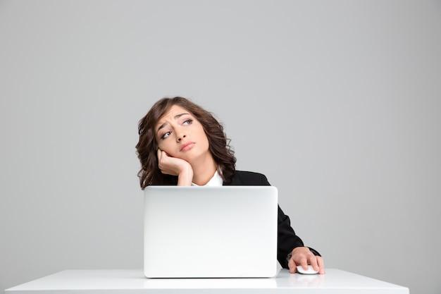 Donna d'affari graziosa riccia depressa triste premurosa che sogna seduta al laptop