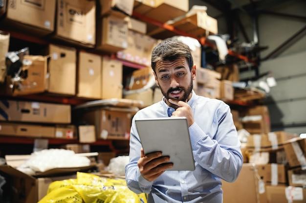 Supervisore premuroso in piedi in magazzino e guardando tablet. è confuso. azienda di spedizioni.