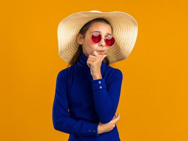 Adolescente premurosa che indossa occhiali da sole e cappello da spiaggia tenendo la mano sul mento guardando in alto isolato sulla parete arancione con spazio di copia