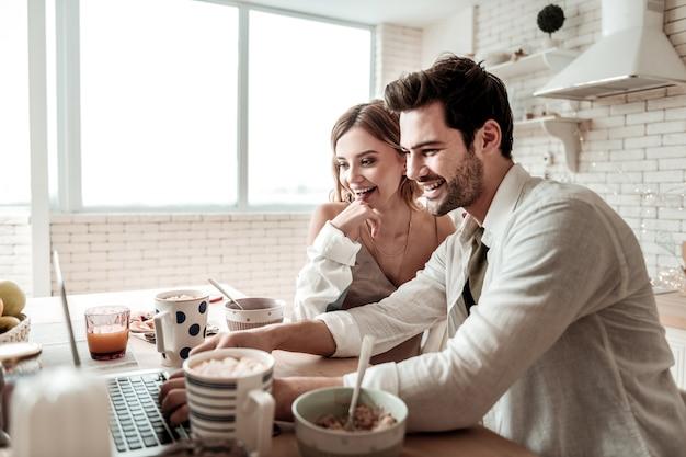 Vista premurosa. donna graziosa raggiante con i capelli lunghi che indossa abiti da casa che sembra seria mentre guarda un video con suo marito