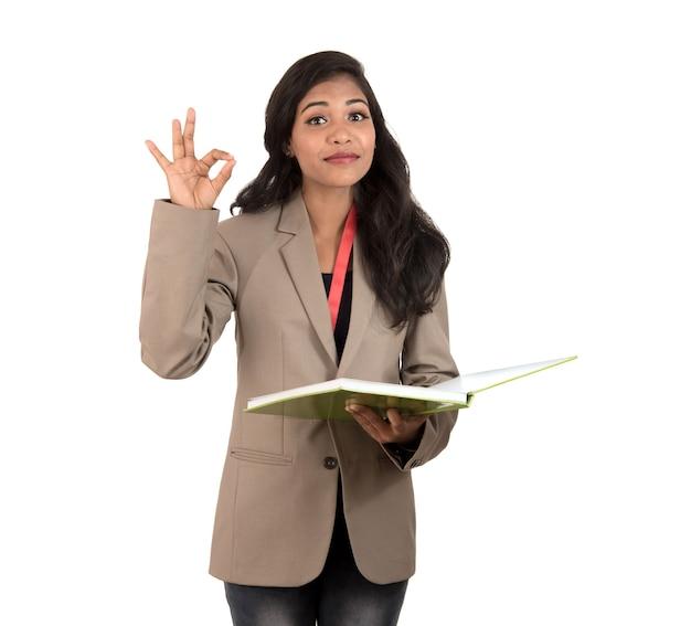 Studente, insegnante o signora premurosa della donna di affari che tiene i libri e che mostra segno giusto su fondo bianco