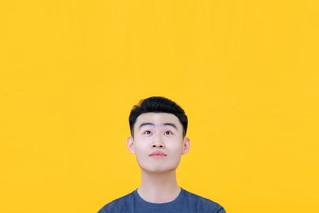 Giovane uomo asiatico premuroso che osserva in su per copiare spazio