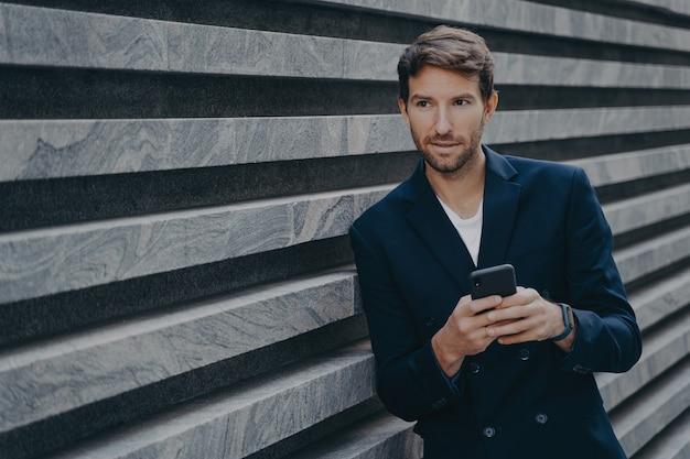 Giovane uomo barbuto premuroso che sta fuori che tiene la digitazione mobile sulla tastiera del telefono