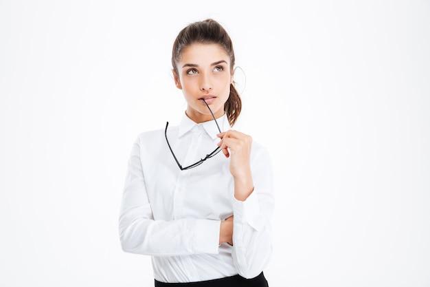 Premurosa giovane donna d'affari che tiene gli occhiali e pensa al muro bianco