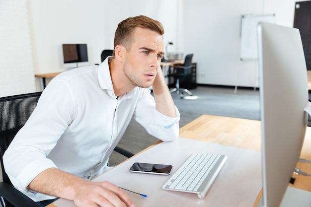 Giovane uomo d'affari premuroso che pensa e usa il computer in ufficio