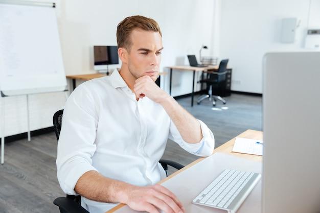 Giovane uomo d'affari premuroso che pensa e usa il computer al lavoro