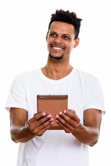 Riflessivo giovane africano felice uomo sorridente mentre si tiene la tavoletta digitale con entrambe le mani