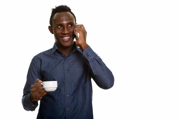 Giovane uomo africano felice premuroso che sorride mentre parlando sul cellulare