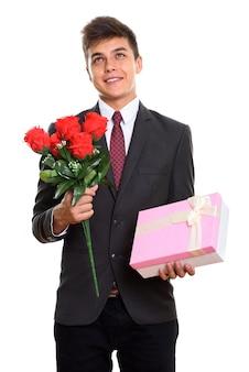 Riflessivo giovane uomo felice sorridente mentre si tiene il mazzo di rose rosse e confezione regalo rosa. concetto di san valentino