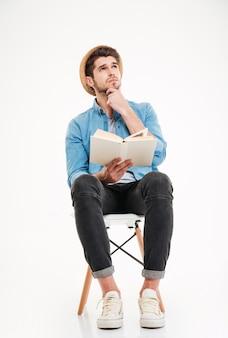 Giovane premuroso in cappello seduto e leggendo un libro a