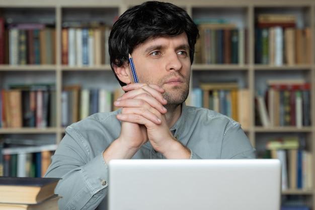 Il giovane premuroso è seduto a una scrivania in ufficio con una matita in mano che guarda lontano dal lavoro su un laptop pensando a un piano di progetto