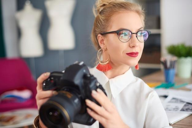 Giovane donna premurosa che tiene la macchina fotografica?
