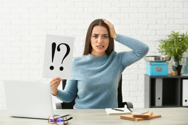 Giovane donna premurosa che tiene foglio di carta con punti esclamativi e interrogativi sul posto di lavoro