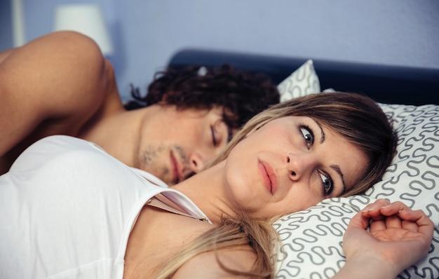 Premurosa giovane donna che guarda lontano mentre giace vicino al suo ragazzo addormentato. relazione di coppia e concetto di problemi.
