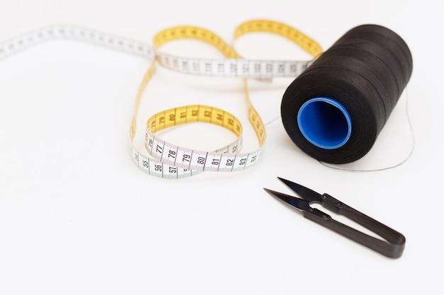 Centimetro e forbici del filo su un fondo bianco. sarta