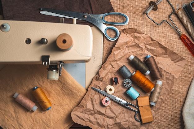 Filo, forbici e forniture per cucire su uno sfondo vintage.