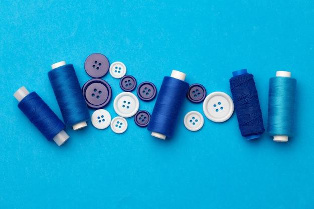 Bobine di filo e pulsanti su sfondo blu
