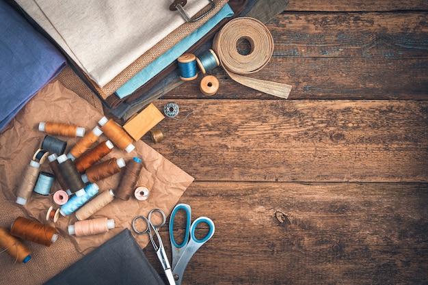 Fili e tessuti di diversi colori, forbici e un ditale con un nastro su uno sfondo di legno. il concetto di cucito.