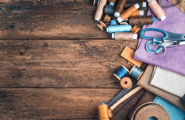 Fili, tessuti, forbici su uno sfondo di legno. vista dall'alto con copia spazio. il concetto di cucito.
