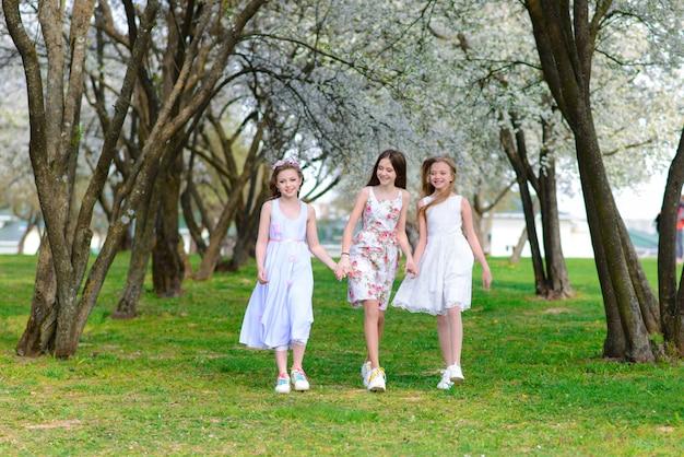 Tre adorabili ragazze in abiti si tengono per mano in giardino, parco.