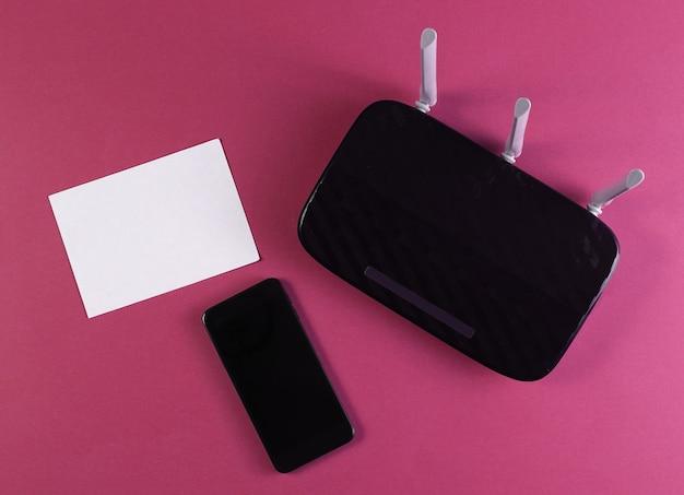 Router wifi a tre antenne con smartphone su colore rosso