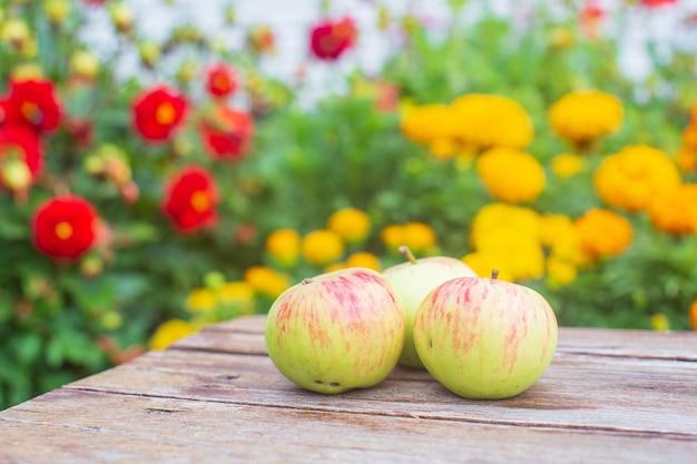 Tre mele giacciono su una superficie di legno sullo sfondo di fiori che sbocciano concetto di cibo sano