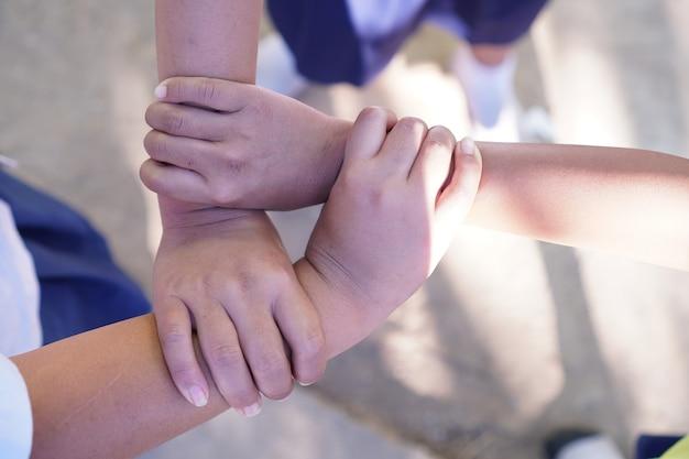 Tre braccia con le mani di ragazze che si tengono l'un l'altra unendo il concetto di lavoro di squadra dell'istruzione