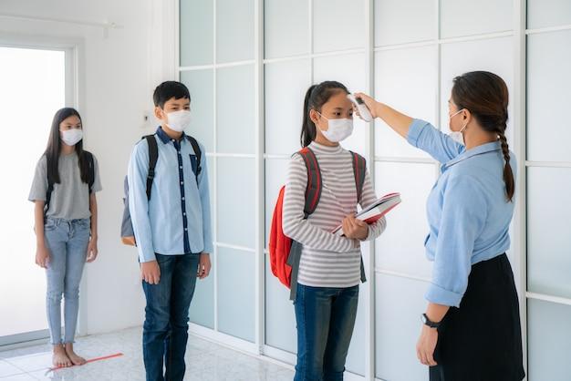 Tre studenti asiatici che indossano una maschera a una distanza di 6 piedi da altre persone mantengono la distanza