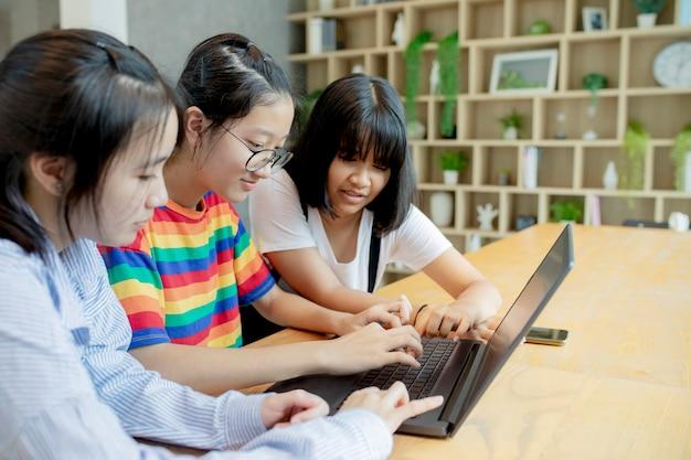 Tre adolescenti asiatici utilizzando il computer portatile nel soggiorno di casa