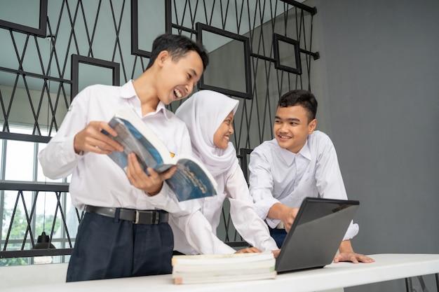 Tre adolescenti asiatici studiano insieme in uniformi scolastiche per chiacchierare mentre usano un laptop e diversi libri