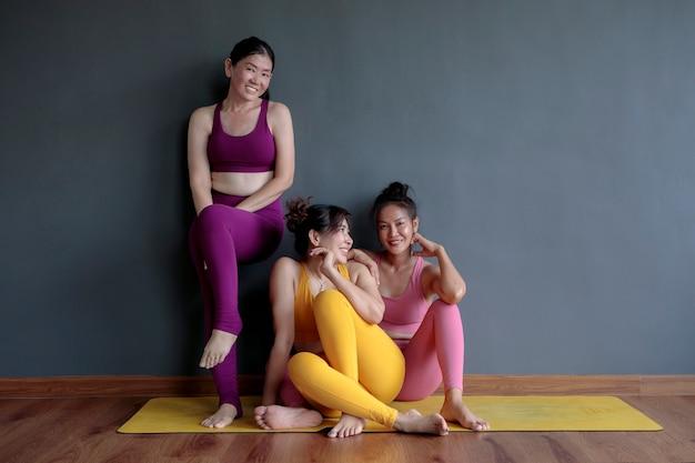 Tre donna asiatica che indossa tuta yoga seduto nella sala fitness