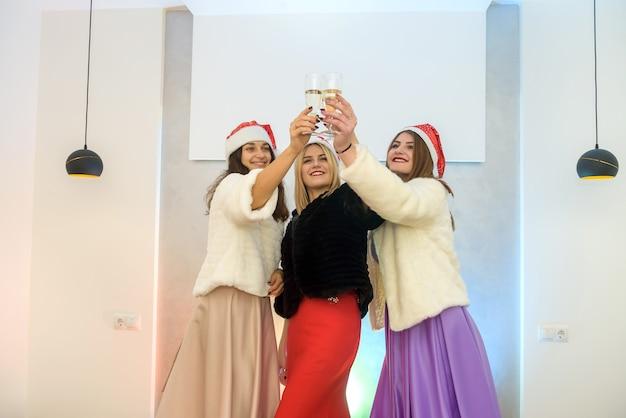 Tre donne attraenti con bicchieri di champagne che brindano alla festa. festa di capodanno