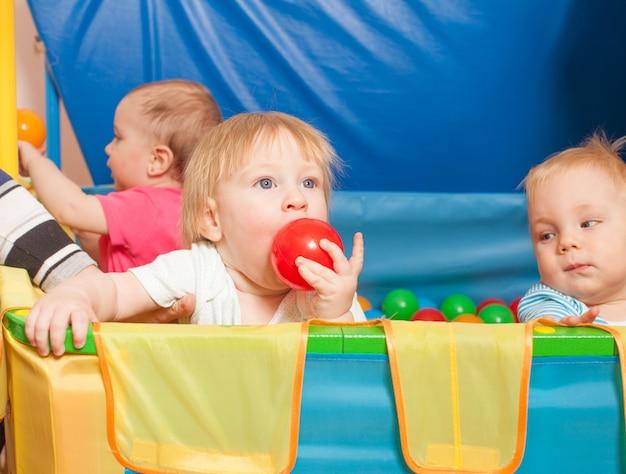 Tre bambini che giocano con palline multicolori all'interno del box
