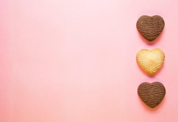 Tre biscotti al forno a forma di cuore su sfondo rosa.