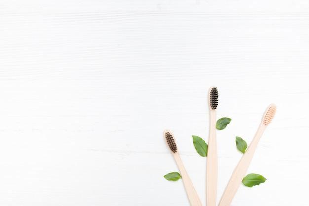 Tre spazzolini da denti di bambù si trovano a ventaglio su uno sfondo di legno chiaro con alberi, concetto senza plastica