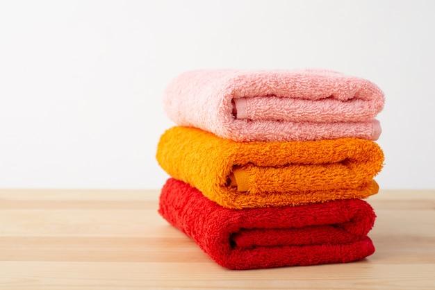 Tre asciugamani da bagno sulla tavola di legno