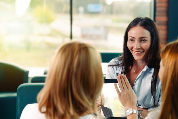 Tre belle ragazze caucasiche che chiacchierano sul divano al caffè insieme. stile di vita aziendale con tecnologia gadget, pmi di avvio, studenti universitari o concetto di donna d'affari di lavoro.