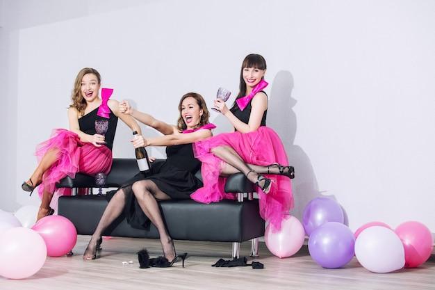 Tre belle donne alla moda divertenti con un bel trucco sorridono, ridono e festeggiano con palloncini