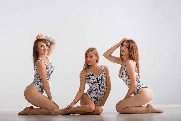 Tre belle ragazze in costume da bagno stanno su uno sfondo grigio